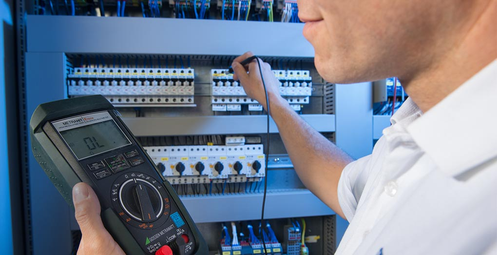 HPS - A worker with a meter on the control cabinet