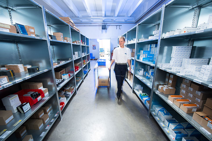 HPS employee puts things on storage shelves