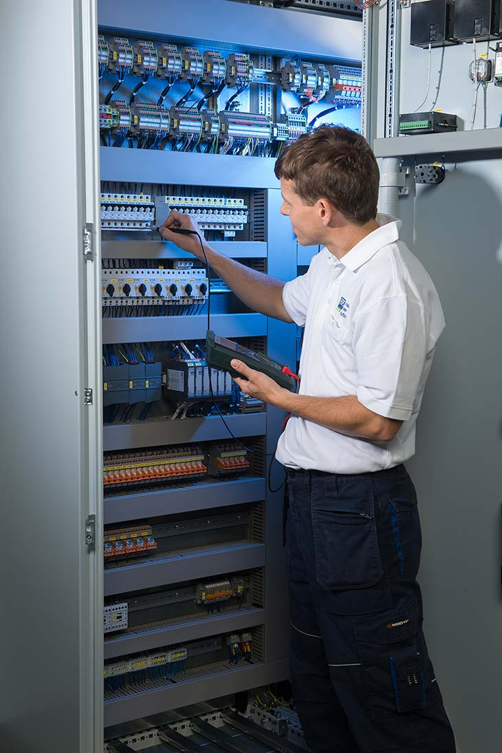 HPS - Employee carries out measurements in a control cabinet